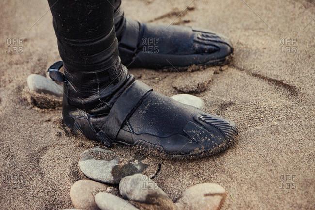 Feet in dive footwear on beach