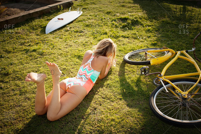 Woman lounging by bike and surfboard