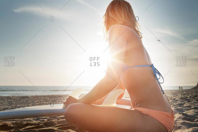 Woman on sun dappled beach with surfboard