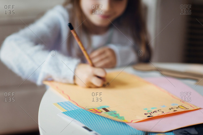 Young girl writing a letter to Santa at Christmas