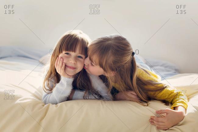 Older sister kissing her younger sister