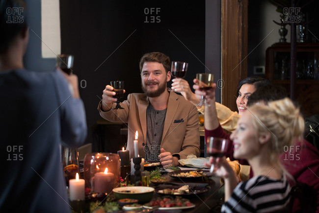 Friends making a toast at a holiday dinner party