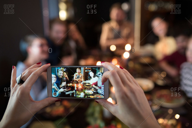 Woman photographing friends during a dinner party