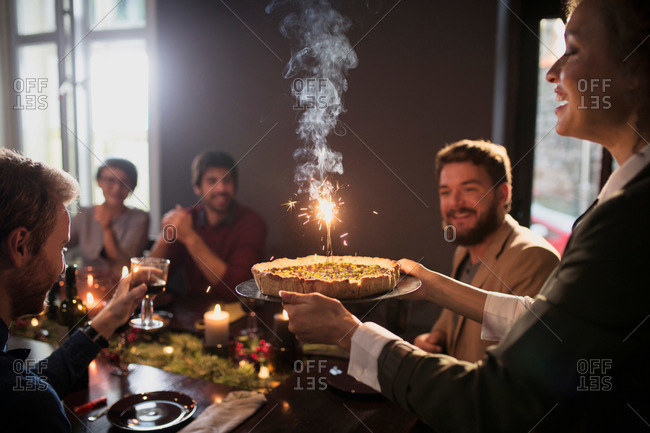 Serving a pie with a sparkler at a holiday party