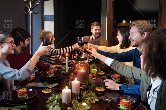 Friends clinking glasses of wine at a holiday dinner party
