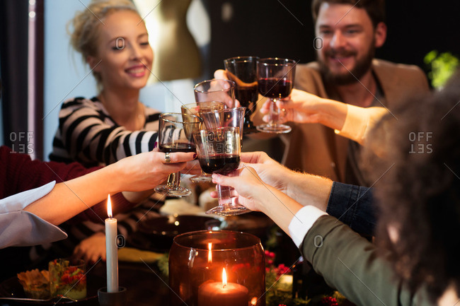 Friends toasting each other at a holiday dinner party