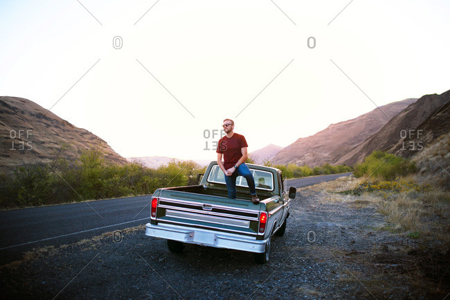 Young man posing on back of vintage pick-up truck