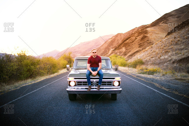Man posing on hood of vintage pick-up truck