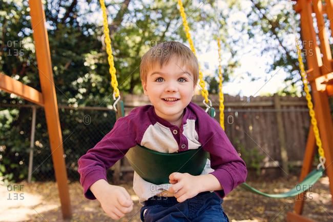 Boy playing on backyard swingset