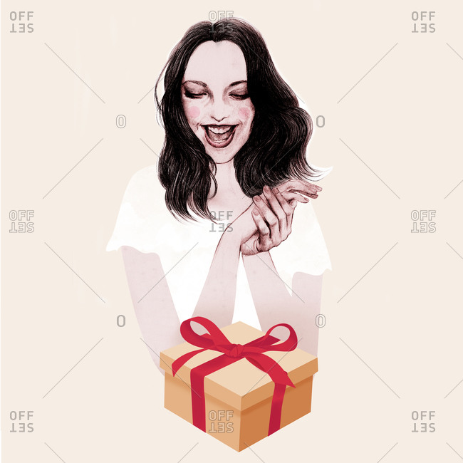 Woman looking at a gift and clasping her hands with joy