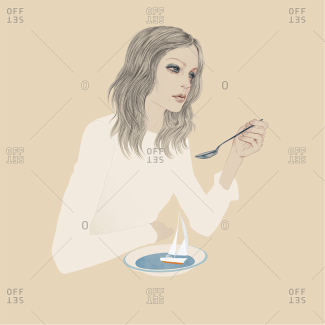 Woman holding a spoon above a bowl with a sailboat