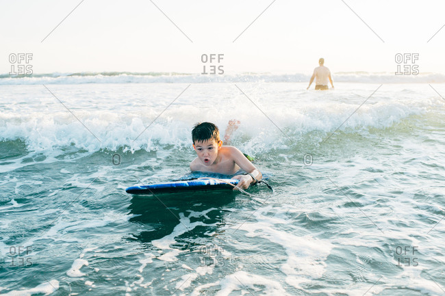 Enthusiastic young boy riding a boogie board in ocean waves
