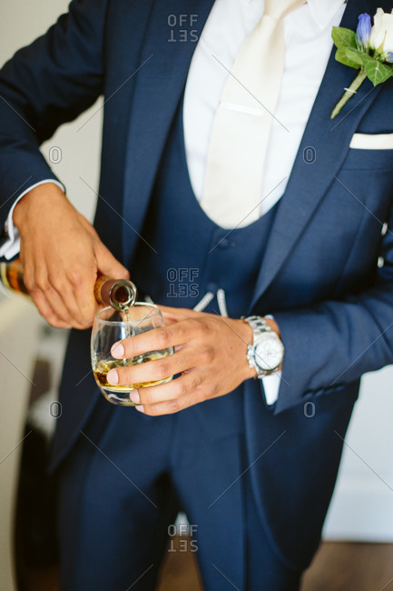 Man in formalwear pours a drink before his wedding