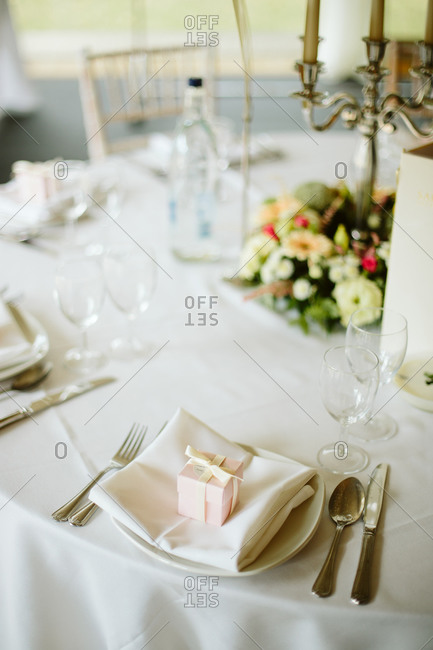 Elegant wedding reception table set with a small boxed gift
