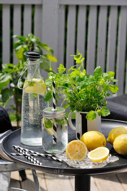 Fresh lemon water and mint on a patio table