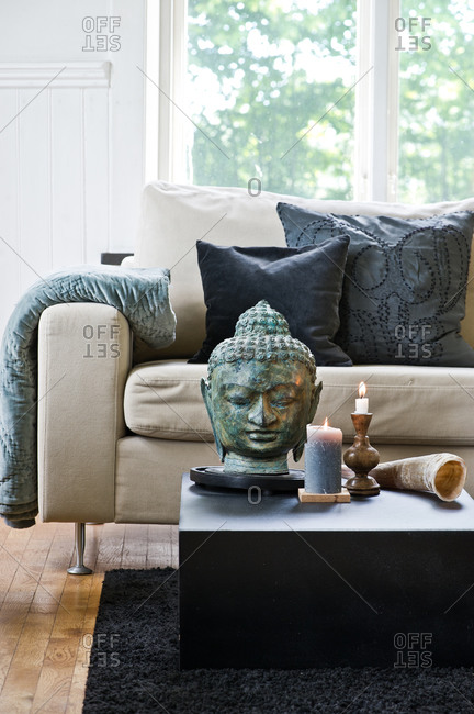 Living room coffee table with Buddha head and lit candles
