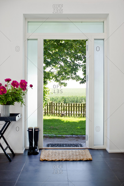 Open front door with a view of green fields