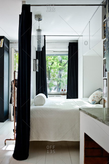 Bed with white linens and black curtains