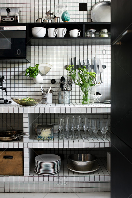 Dishes on shelves in a square-tiled kitchen