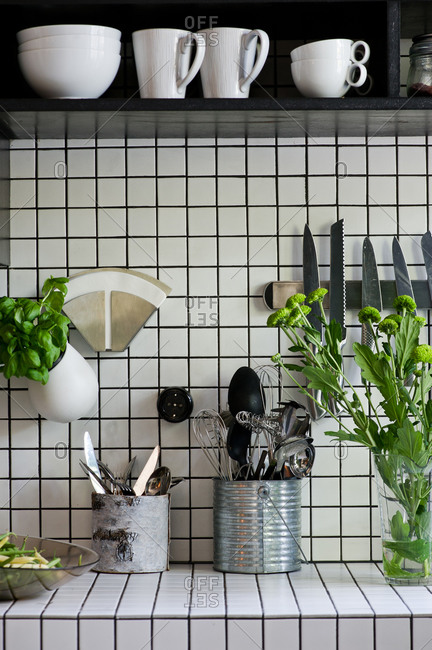 Herbs and utensils in a square-tiled kitchen