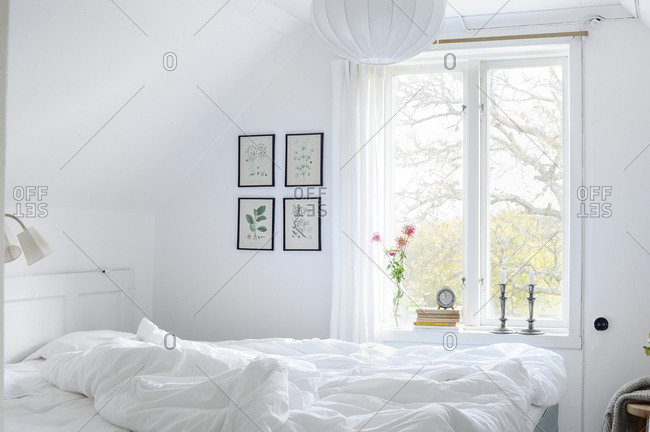 Unmade white bed in a white bedroom
