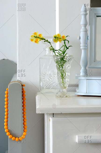 Fresh flowers and orange beaded necklace on a dresser
