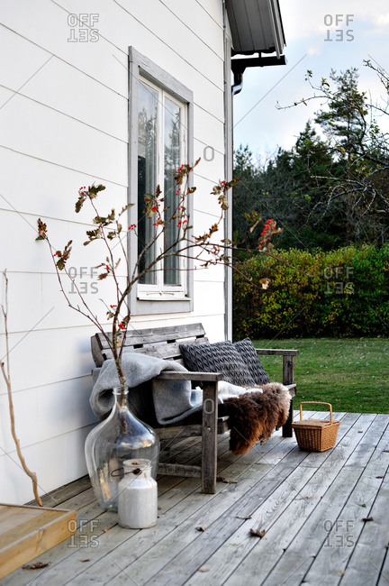Rustic wooden bench with fur blankets and pillows