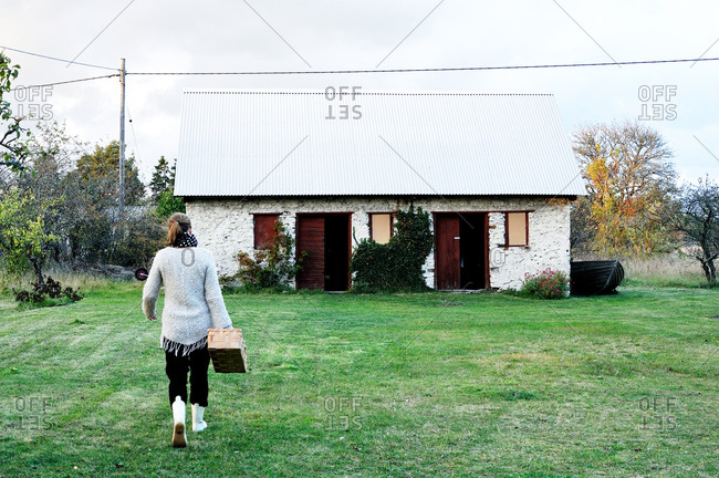 Woman carrying a basket to a rustic stone barn