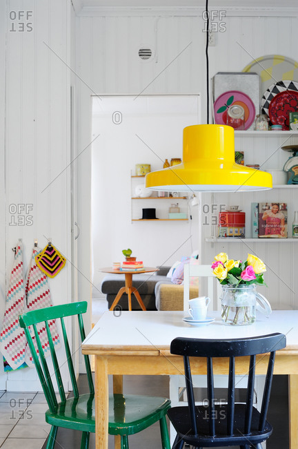 Simple dining table with colorful chairs and accents