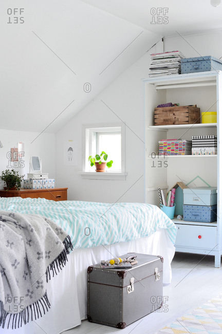 Bed and bookshelf in a white bedroom