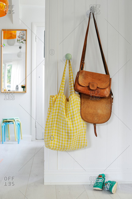 Bags hanging on pegs in a white foyer