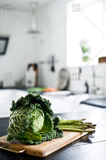 Head of cabbage and asparagus on a wooden cutting board