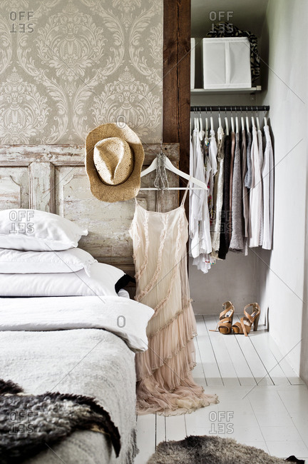 Retro dress and straw hat hanging on a rustic headboard