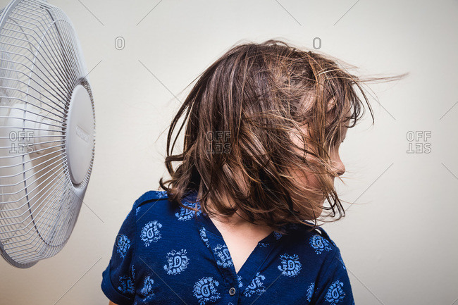 Cute young girl turning her head to enjoy breeze from fan