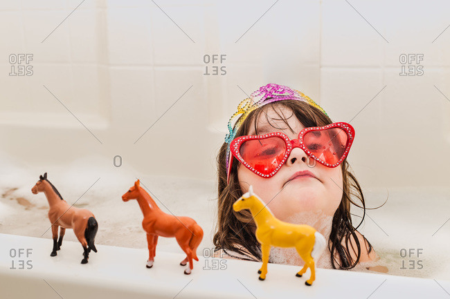 Little girl with sunglasses, tiara and toy horses in bathtub