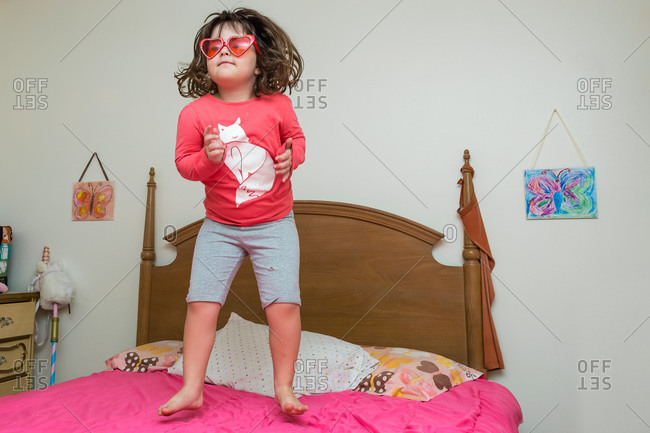 Vivacious young girl in heart glasses jumping on her bed