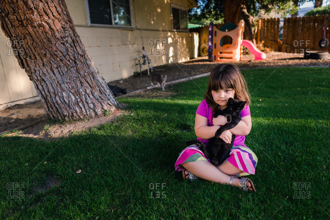 Portrait of young girl sitting in backyard holding black kitten