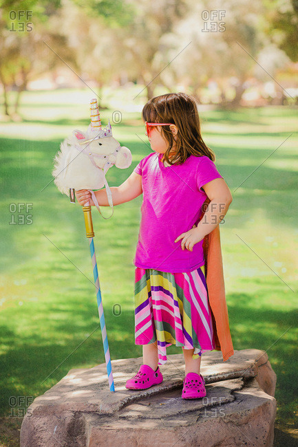 Colorfully dressed young girl playing on rock with unicorn hobby horse