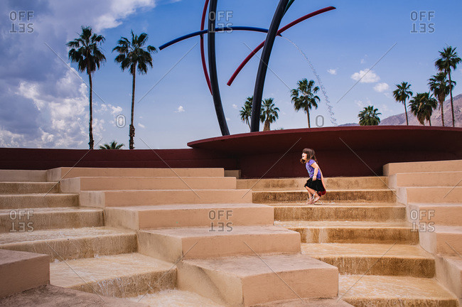 Young girl playing on steps of a fountain