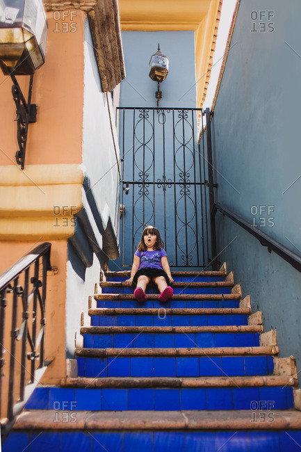 Little girl sitting at the top of a blue tiled staircase