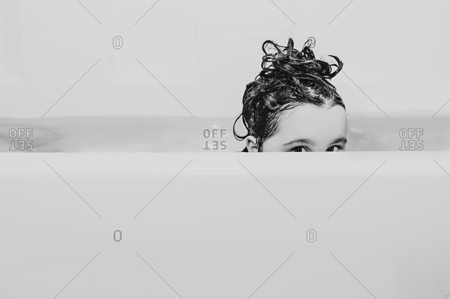 Young child in bathtub with shampoo in her hair