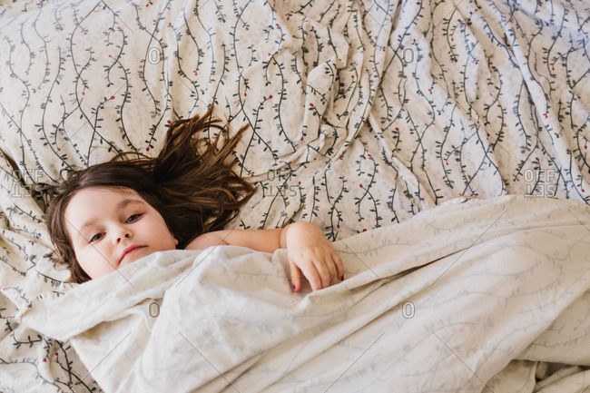 Overhead view of young girl relaxing in bed