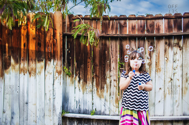 Young girl blowing bubbles near a weathered wooden fence