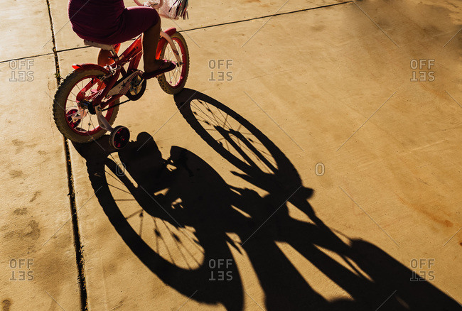 Shadow of young girl riding a bicycle with training wheels