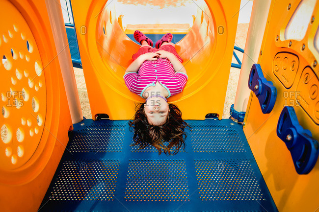 Young girl lying upside down in playground tunnel