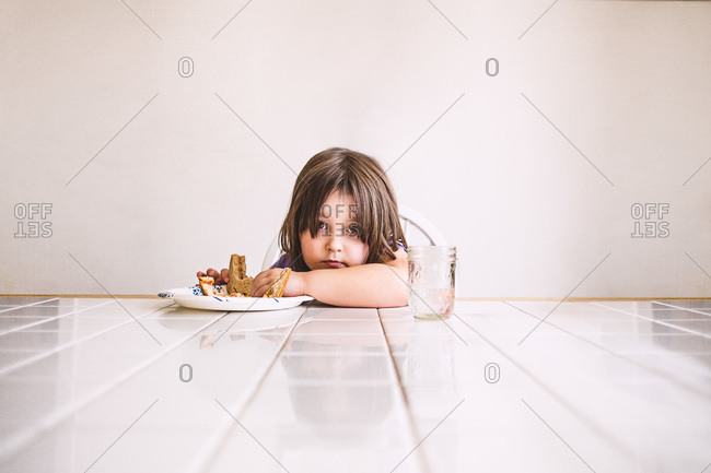 Young child eating sandwich at white tiled table