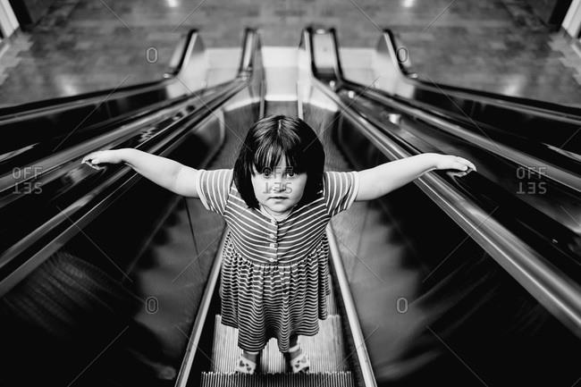 High angle view of young girl riding an escalator