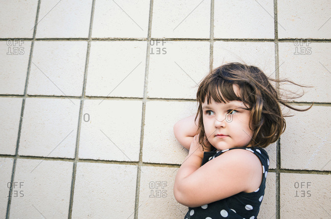 Portrait of a cute little girl against a tile wall