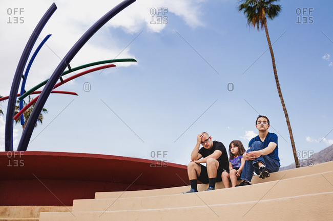 Portrait of young girl and her two older brothers on steps next to modern sculpture