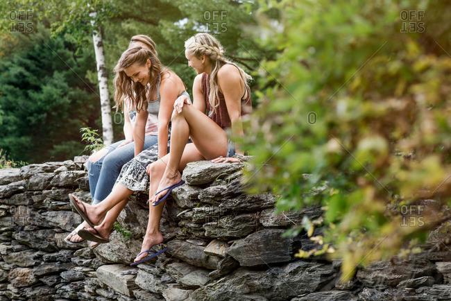 Three female friends on a stone wall